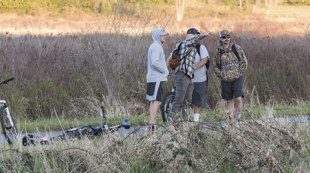 Bike riders watch from the Centennial Trail as multiple strike teams from Snohomish County fire departments fight a large brush fire along Highway 9 on Wednesday in Bryant. (Andy Bronson / The Herald)