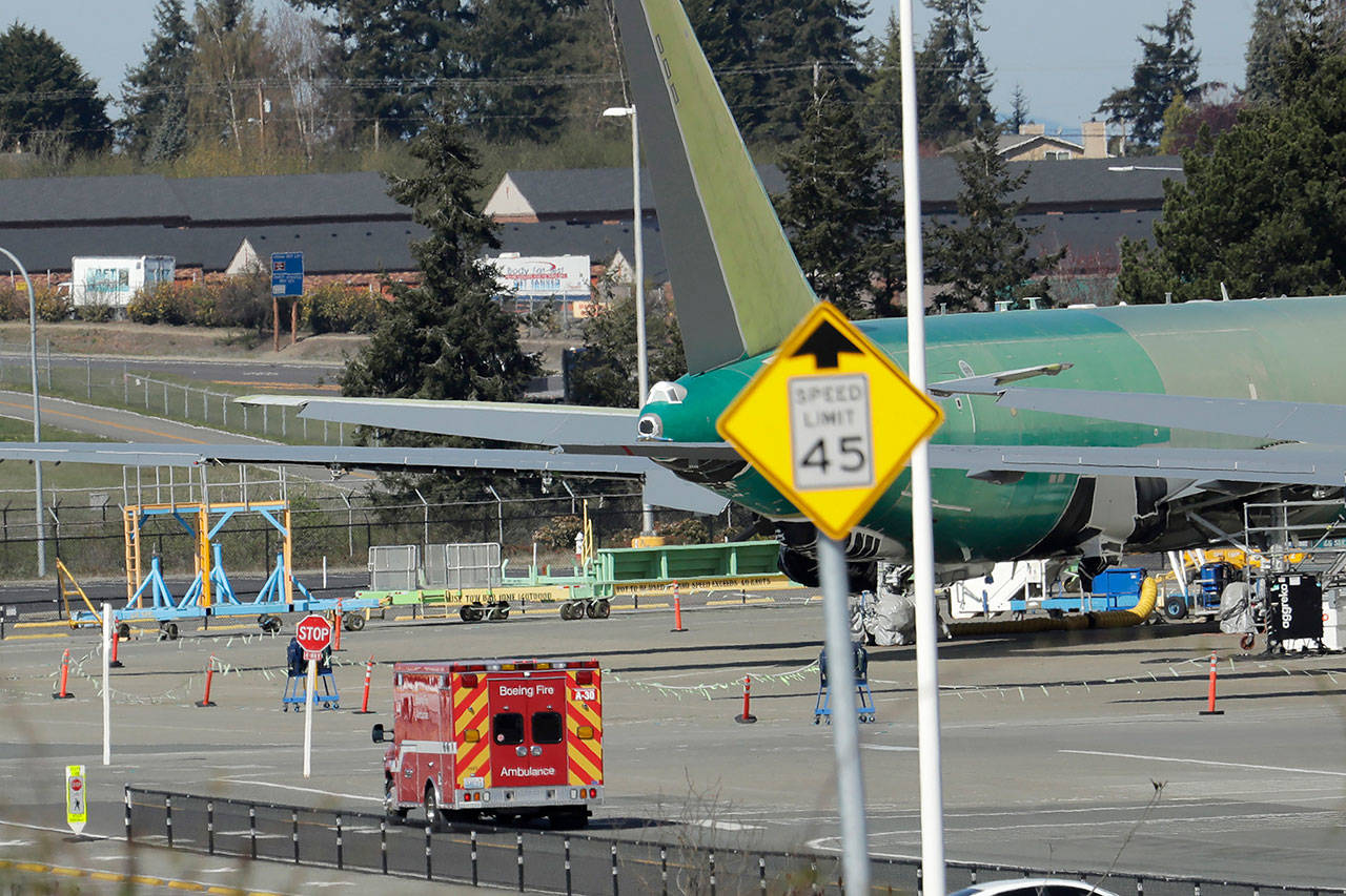A Boeing Fire Dept. ambulance drives slowly past a U.S. Air Force KC-46 tanker being built by Boeing on Monday at Boeing's airplane assembly facility in Everett. (AP Photo/Ted S. Warren)
