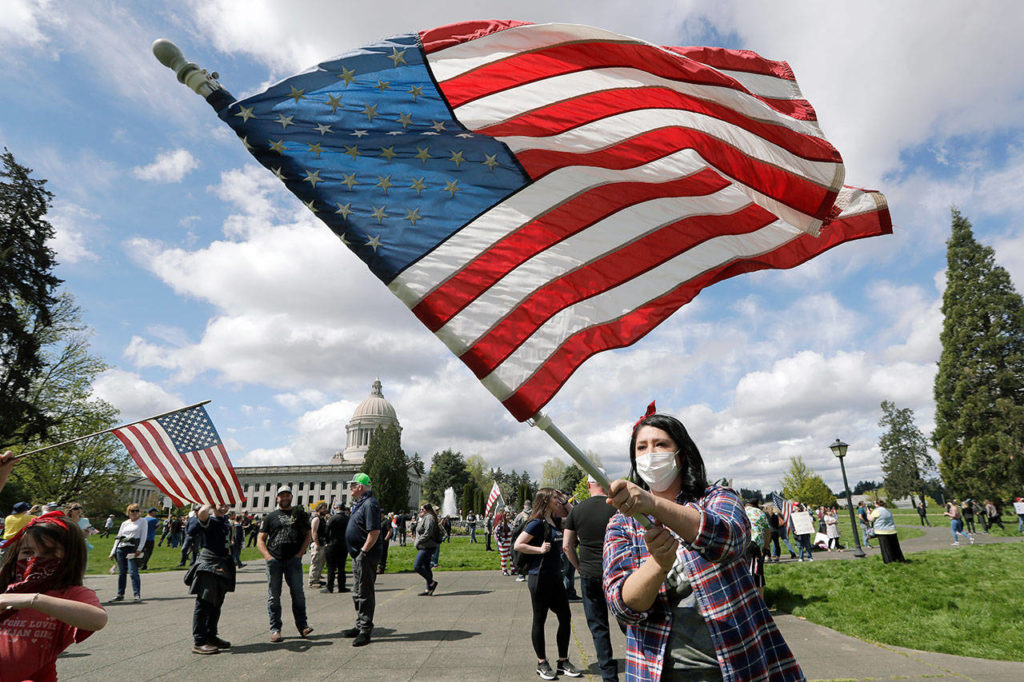Janell Sorensen, of Woodland, waves a flag Sunday as demonstrators begin to gather at the Capitol in Olympia for a protest opposing Washington state's stay-home order to slow the coronavirus outbreak. (AP Photo/Elaine Thompson)