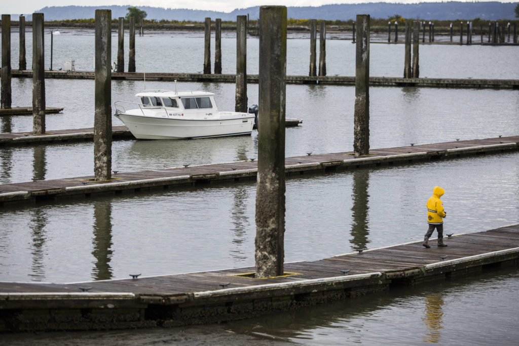 A boy walks along one of the empty docks at the 10th Street Boat Launch in Everett. (Olivia Vanni / The Herald)