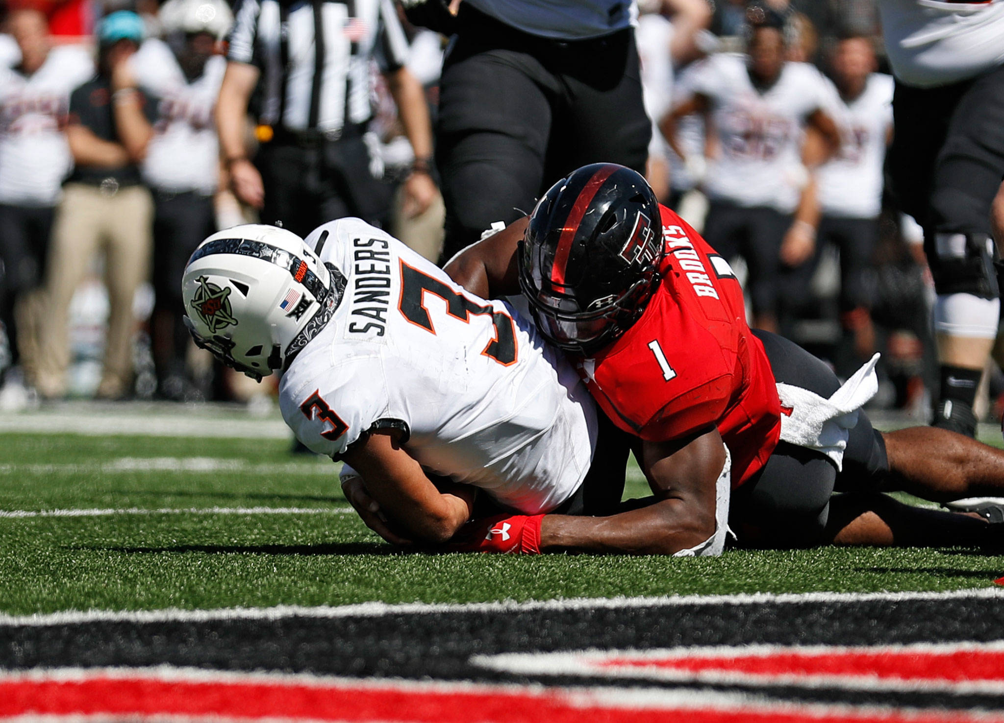 Texas Tech's Jordyn Brooks (1) tackles Oklahoma State's Spencer Sanders to stop a two-point conversion during the second half of a game Oct. 5, 2019, in Lubbock, Texas. (AP Photo/Brad Tollefson)