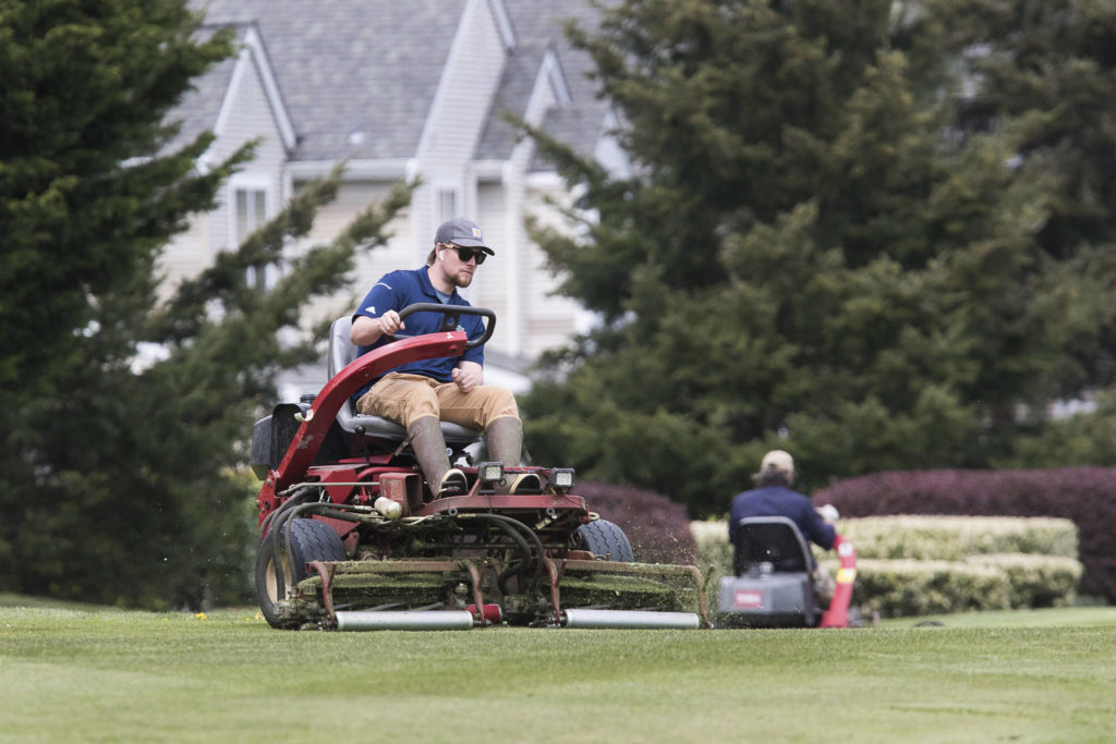 Mike Season (left) and Dan Radke mow grass Friday at Harbour Pointe Golf Course in Mukilteo. Local golf courses are getting ready in hopes of opening back up on May 5, the first day they're allowed to under Gov. Jay Inslee's modified public health closures. (Andy Bronson / The Herald)