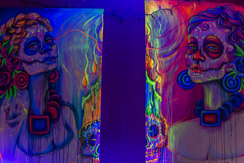 A pair of blacklight reactive acrylic paintings she recently sold hang in her studio on Sunday in Everett. Her art is her main source of income which has been hard to sell with to events being cancelled due to COVID-19. (Olivia Vanni / The Herald)