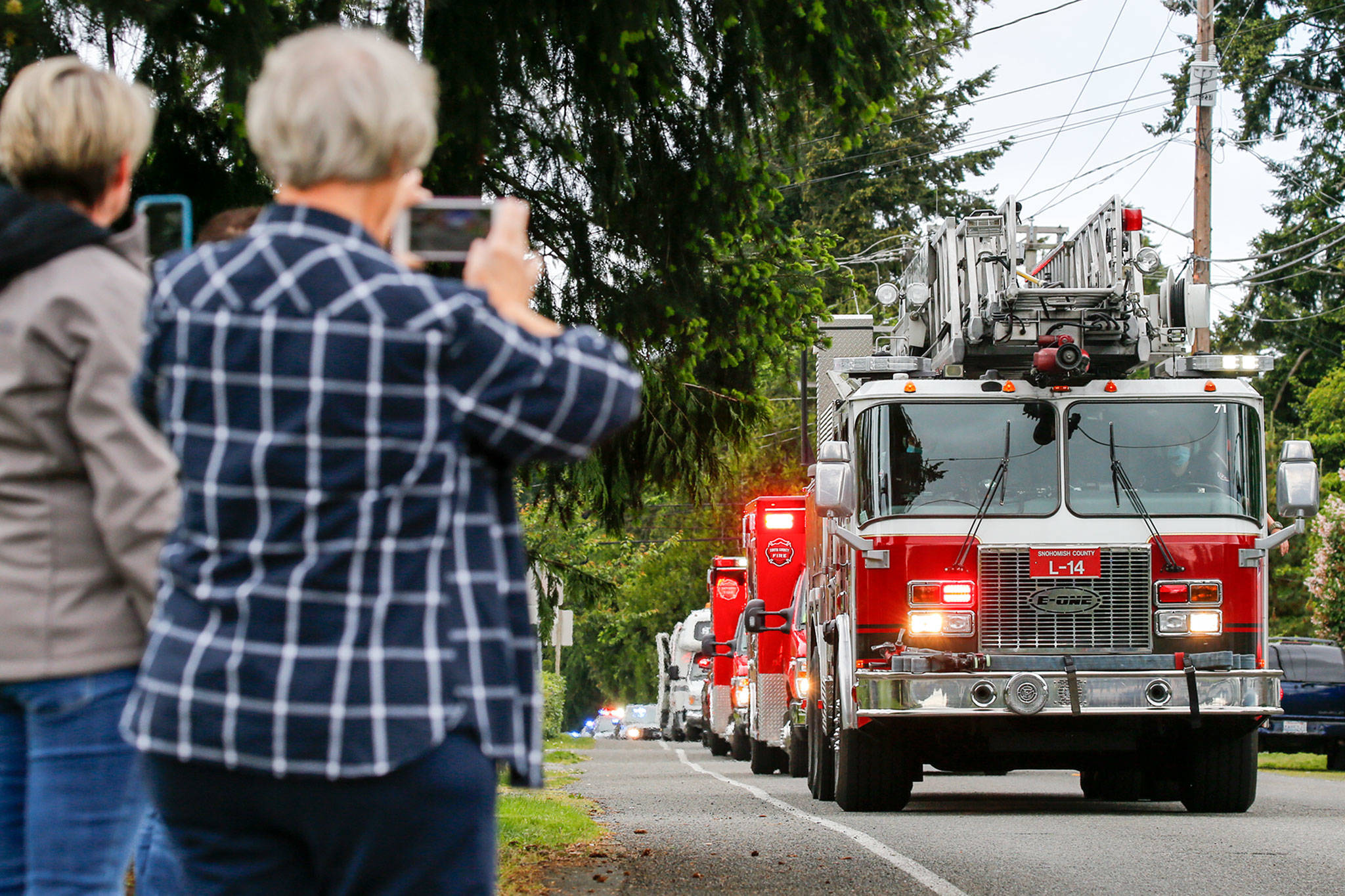 First responders parade past Eli Kincaid's home Tuesday afternoon in Lynnwood. Before the pandemic, Eli's family had planned a Make-a-Wish trip to Disneyland. (Kevin Clark / The Herald)