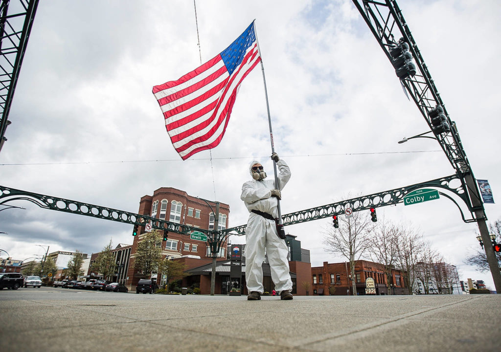Kevin Moeller stands on the corner or Colby and Hewitt avenues in Everett, waving an American flag in support of troops. (Olivia Vanni / The Herald)