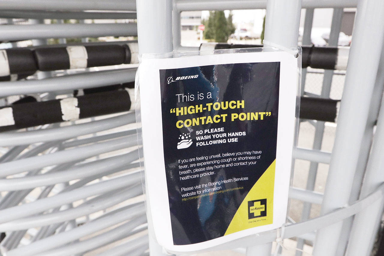 A sign posted at an entry gate of the Boeing plant in Everett advises employees to wash hands after passing through. (AP Photo/Elaine Thompson)