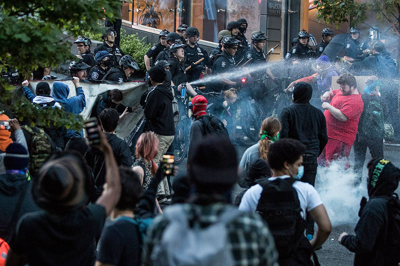 In this May 29, 2020, photo, police push back demonstrators after objects were thrown at them at 5th Avenue and Madison Street during a march in solidarity with Minneapolis and protesting police brutality in Seattle. Protests have been erupting all over the country after George Floyd died earlier this week in police custody in Minneapolis. (Amanda Snyder/The Seattle Times via AP)