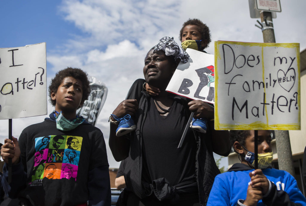 Adja Maïmouna Fame (center) becomes emotional as she stands with her three sons, Djibril Garcia (left), Kamil Garcia (top) and Kareem Garcia during the Black Lives Matter protest on Saturday in Everett. (Olivia Vanni / The Herald)