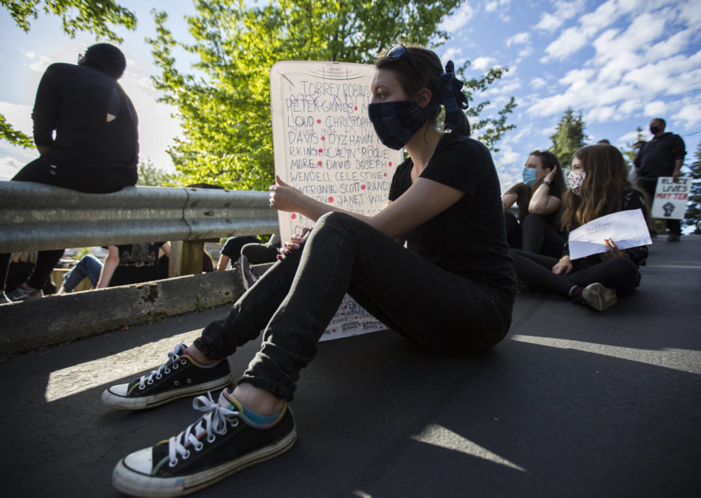 Kylara Triel uses her sign to shield herself from the sun during the Black Lives Matter protest on Sunday in Mukilteo. (Olivia Vanni / The Herald)