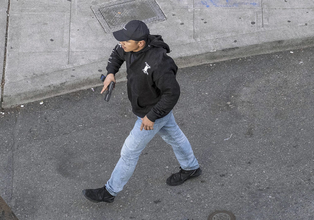 A man holds what appears to be a firearm after having driven at George Floyd protesters Sunday in Seattle. (Dean Rutz/The Seattle Times via AP)