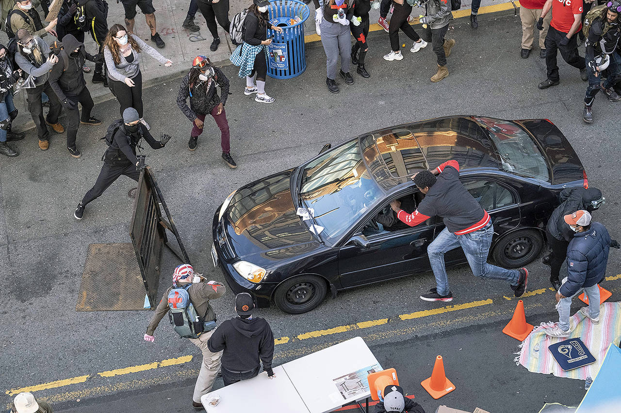 A man drives into the crowd at 11th and Pike, injuring at least one person, before exiting the car and brandishing an apparent firearm Sunday in Seattle during protests over the death of George Floyd in Minneapolis. (Dean Rutz/The Seattle Times via AP)