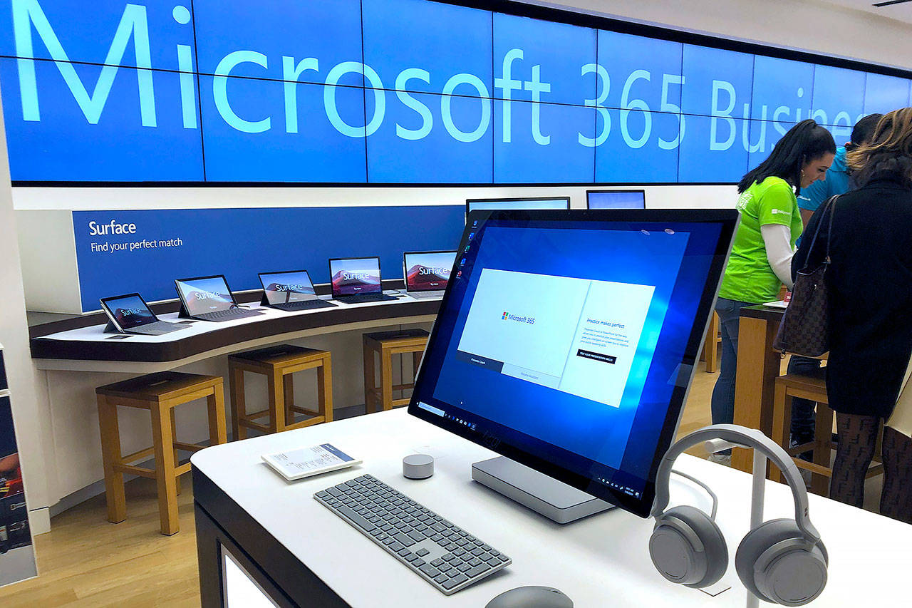 In this Jan. 28 photo, a Microsoft computer is among items displayed at a Microsoft store in suburban Boston. Microsoft said Friday it is permanently closing nearly all of its physical stores around the world. (AP Photo/Steven Senne, File)