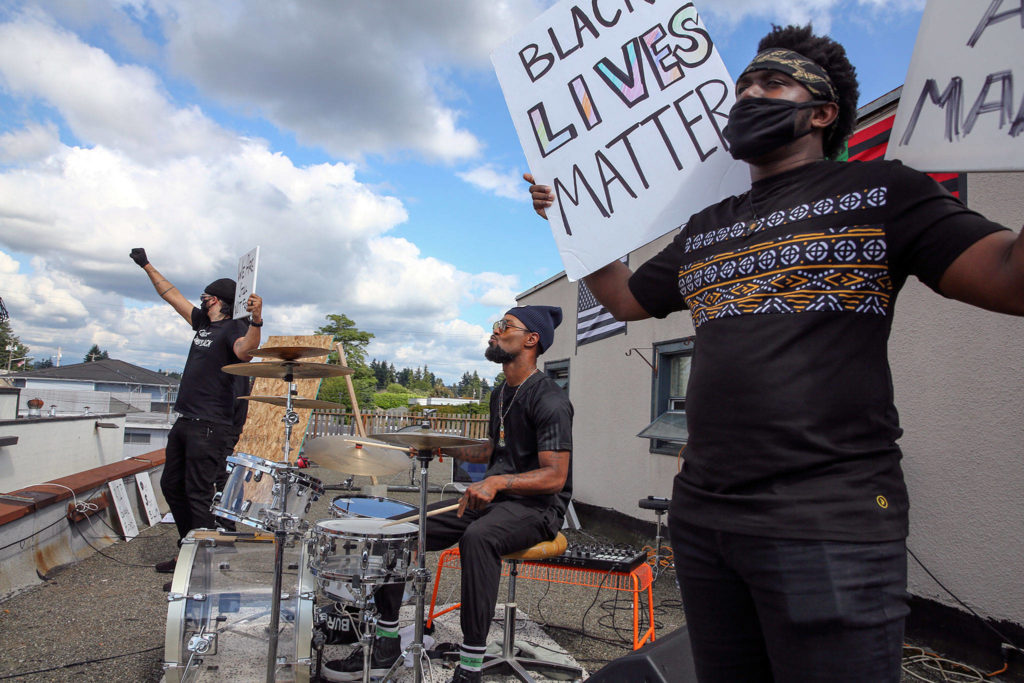 Jordon Jeffries (left), Chris Anderson (center) and Xavier Bennett rally on a rooftop for Black Lives Matter on July 4 in Marysville. (Kevin Clark / The Herald)