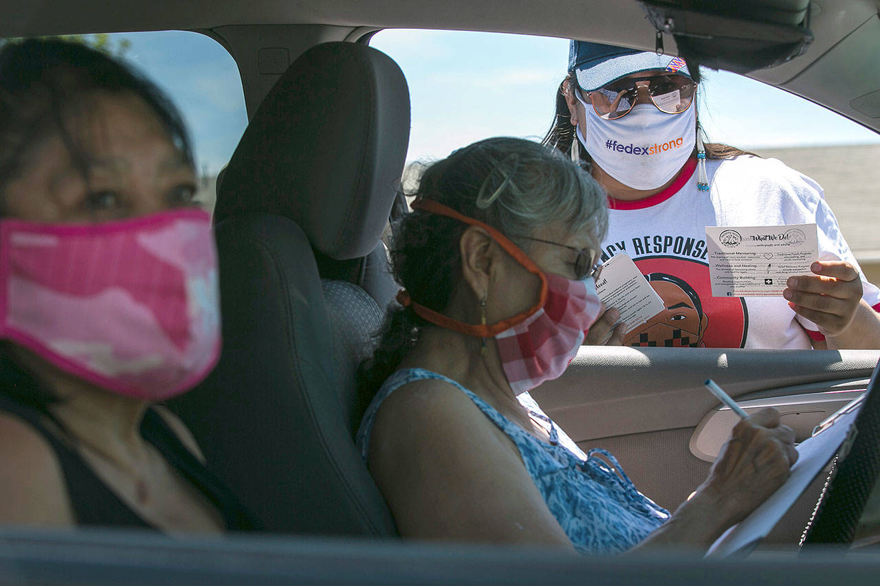Natasha Scott (right) provides information about the Peacekeeper Society to Patricia Randall (center) and Floraine Gardee during a drive-thru distribution of food and emergency supplies at Harrah City Hall in Harrah, Washington. (Amanda Ray/Yakima Herald-Republic via AP)