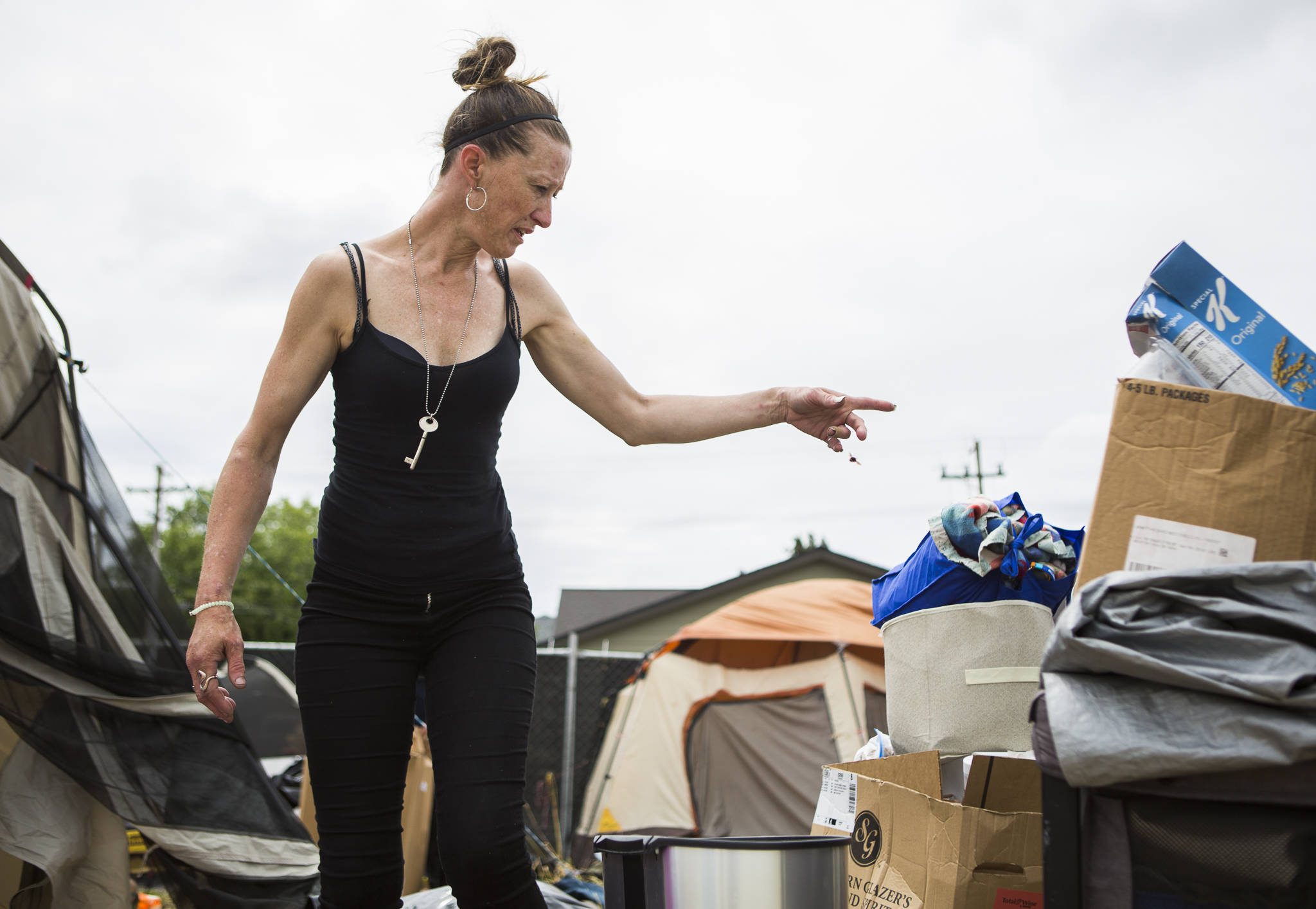 Kimberly Bailey organizes her belongings as she packs to leave her camp on Thursday in Everett. (Olivia Vanni / The Herald)