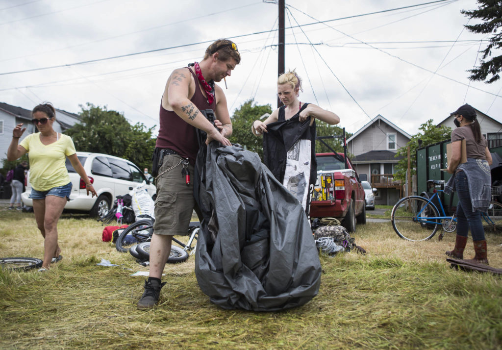 Jack Travis gets help packing up his tent at the Rucker Avenue homeless camp on Thursday in Everett. (Olivia Vanni / The Herald)