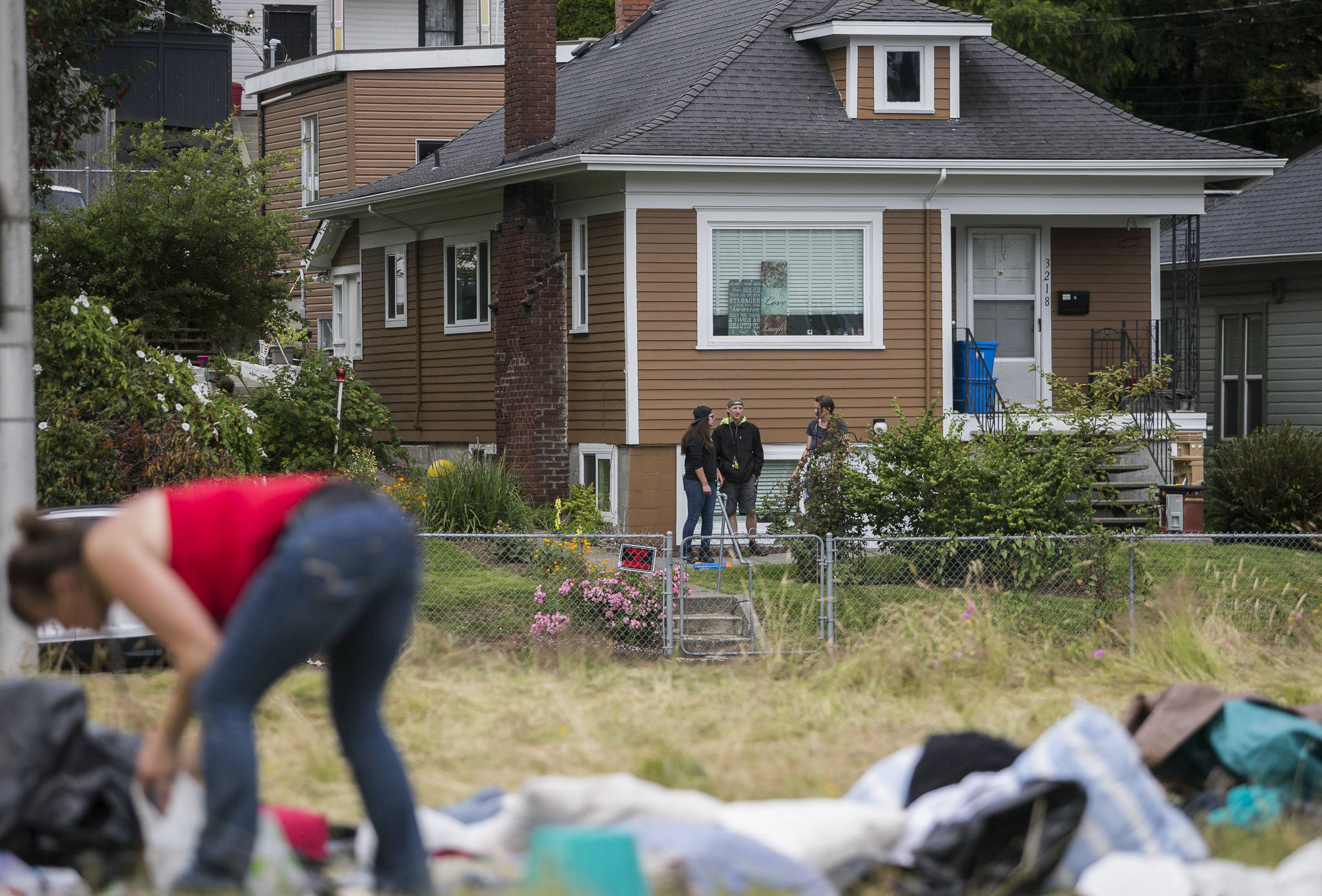 Neighbors watch as people clean and gather their belongings at a homeless encampment on Thursday in Everett. (Olivia Vanni / The Herald)