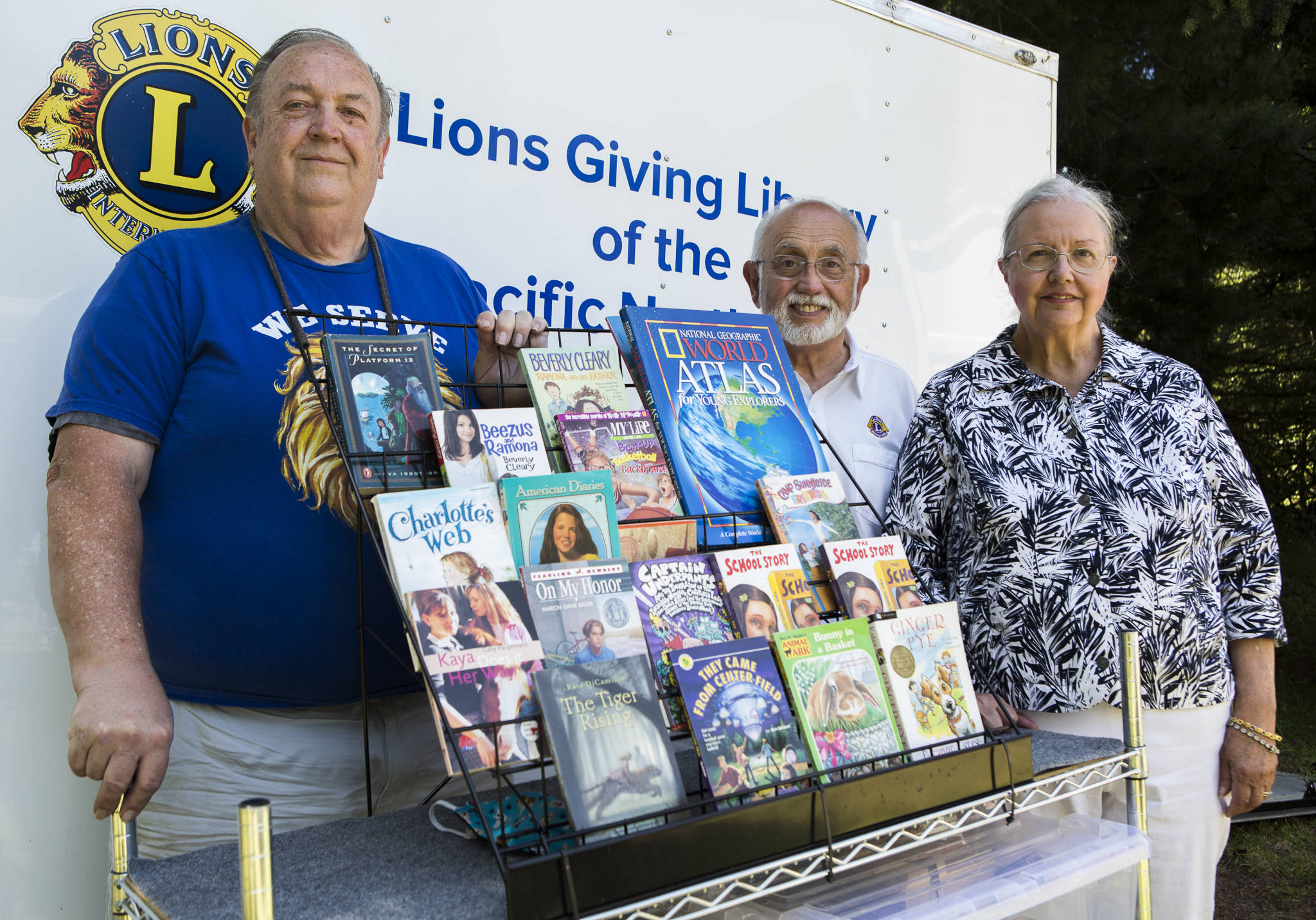 Lions Club members Michael Lally (left), Art Ruben and Judith Ruben with a selection of their donated books on Tuesday in Tulalip. (Olivia Vanni / The Herald)