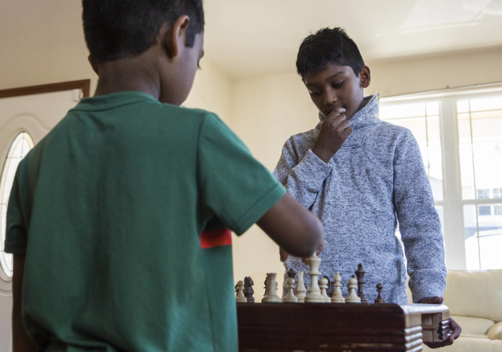 Keshav Beegala (right) plays a practice chess match with his brother Dhruv, 6, in Bothell. (Olivia Vanni / The Herald)