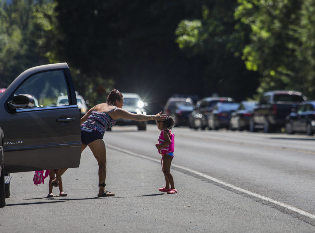 A woman reaches out to pull a young girl away from the fog line along U.S. 2 as cars speed by Wednesday in Index. (Olivia Vanni / The Herald)