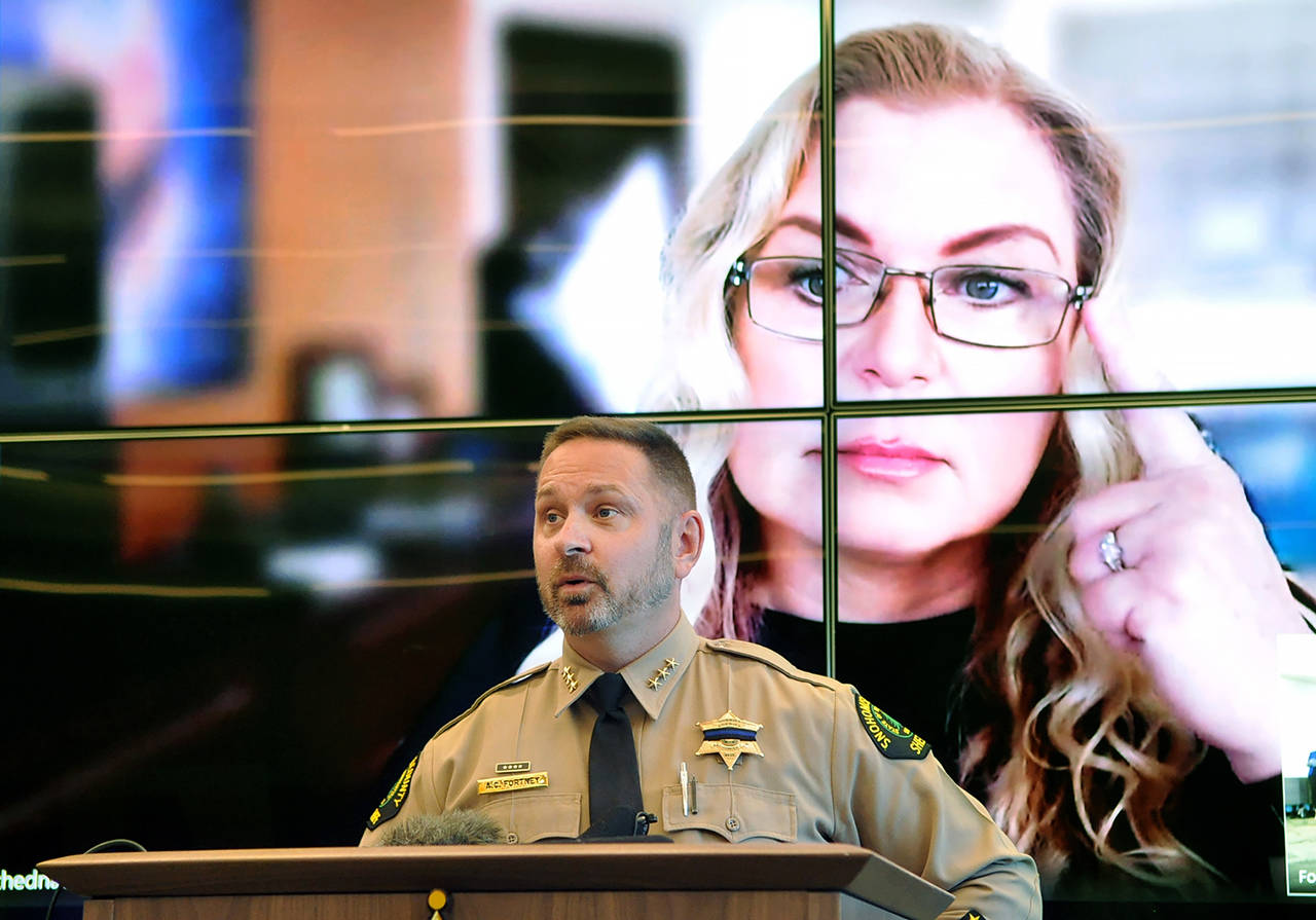 Snohomish County Sheriff Adam Fortney speaks to media Wednesday, with genetic genealogist CeCe Moore participating over Skype on the screen behind him. (Sue Misao / The Herald)