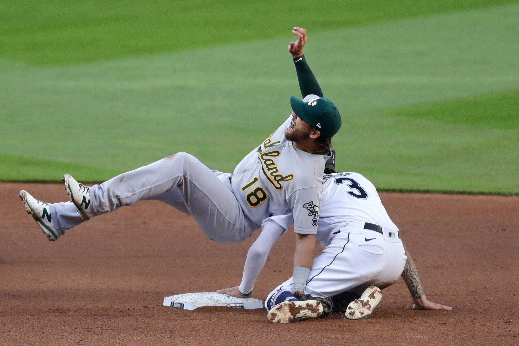 Athletics second baseman Chad Pinder (18) falls on the Mariners' J.P. Crawford after tagging Crawford out at second base on a stolen-base attempt during the fifth inning of a game Aug. 1, 2020, in Seattle. (AP Photo/Elaine Thompson)