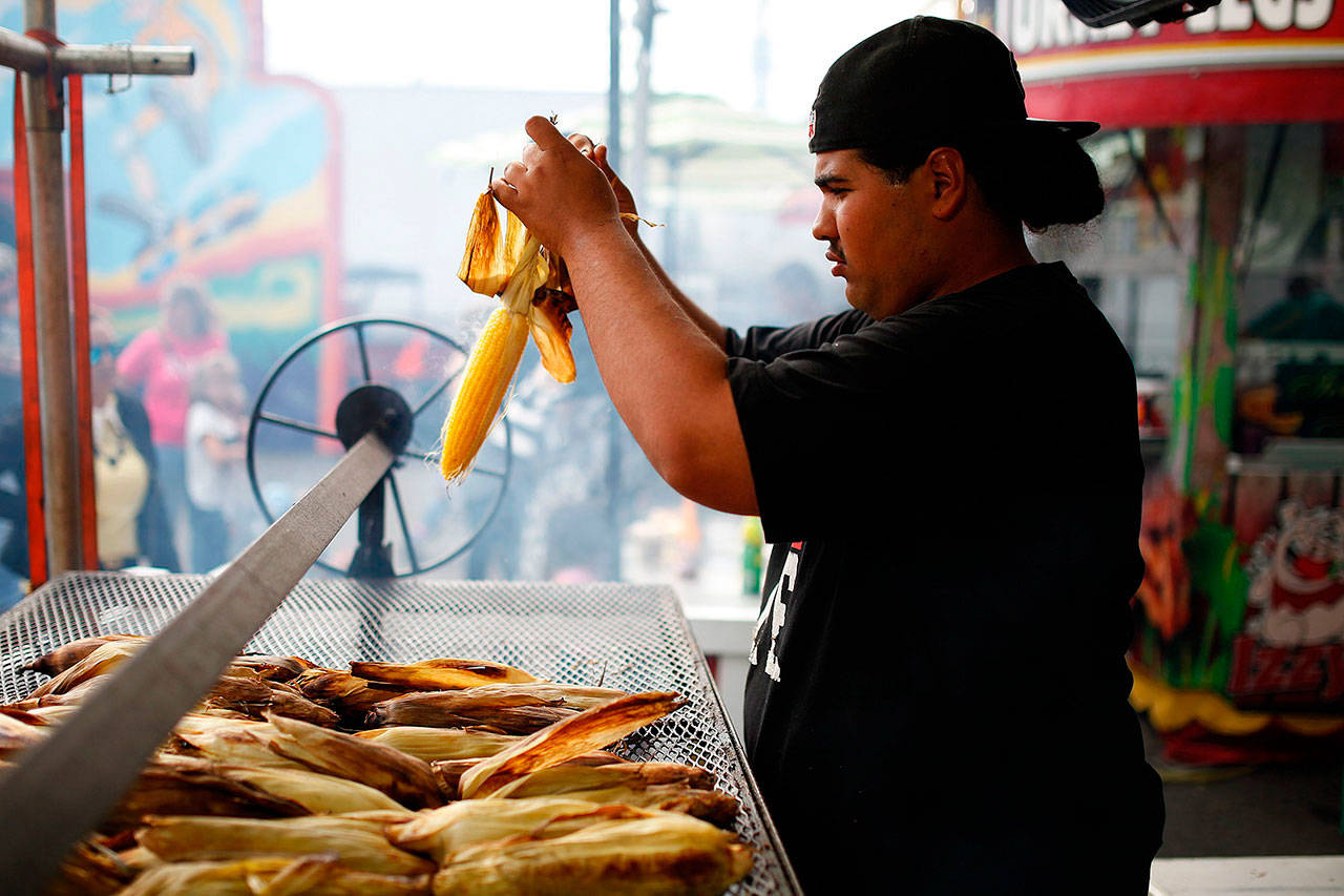 Art Rosales prepares an ear of roasted corn for a customer at Izzy's Barbecue stand at the Evergreen State Fair in Monroe in September 2015. The fair has been cancelled this year because of the pandemic, but a food drive is planned Thursday at the fairgrounds parking lot to help supply local food banks. (Ian Terry / Herald file photo)