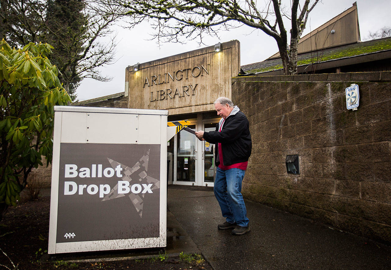 Kevin Duncan puts his ballot in the ballot drop box outside of the Arlington Library on Feb. 11 in Arlington. (Olivia Vanni / The Herald)