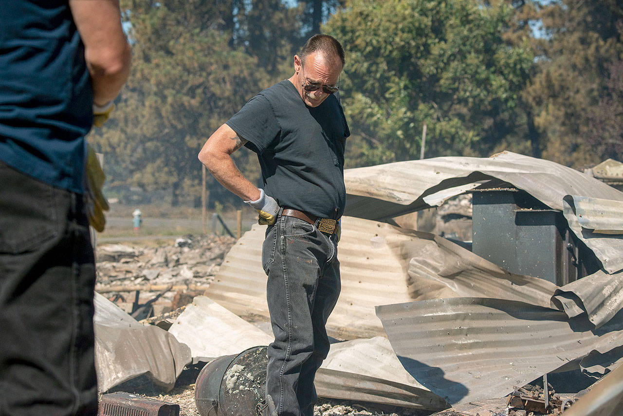 """Jim Murray on Tuesday surveys his house, which was destroyed by a wildfire in Malden in eastern Washington, about 30 miles south of Spokane. """"My wife and I planned to retire here but I'm not sure I am going to rebuild,"""" he said. """"I have a feeling this is going to be a ghost town now."""" (AP Photo/Jed Conklin)"""