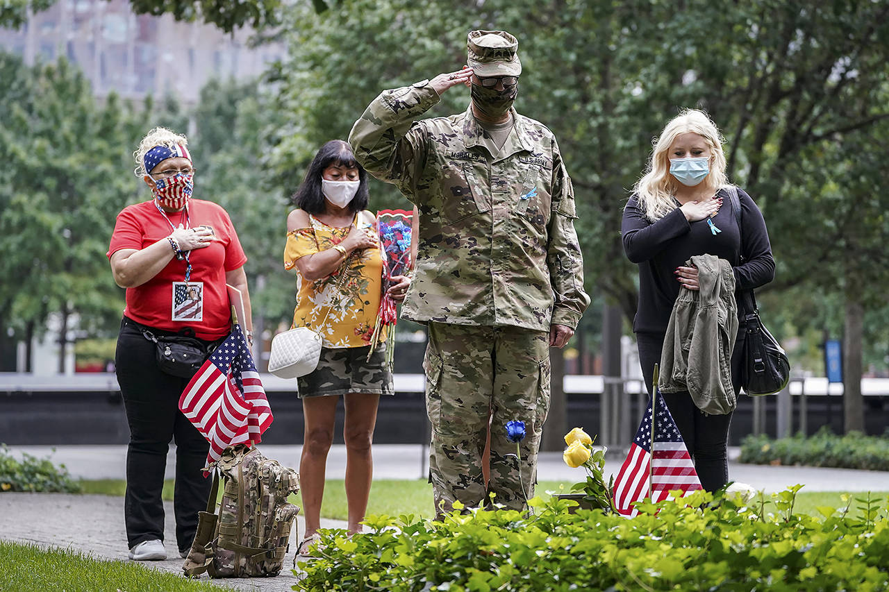 U.S. Army Sgt. Edwin Morales (center right) salutes after placing flowers for fallen FDNY firefighter Ruben D. Correa at the National September 11 Memorial and Museum on Friday in New York. (AP Photo/John Minchillo)