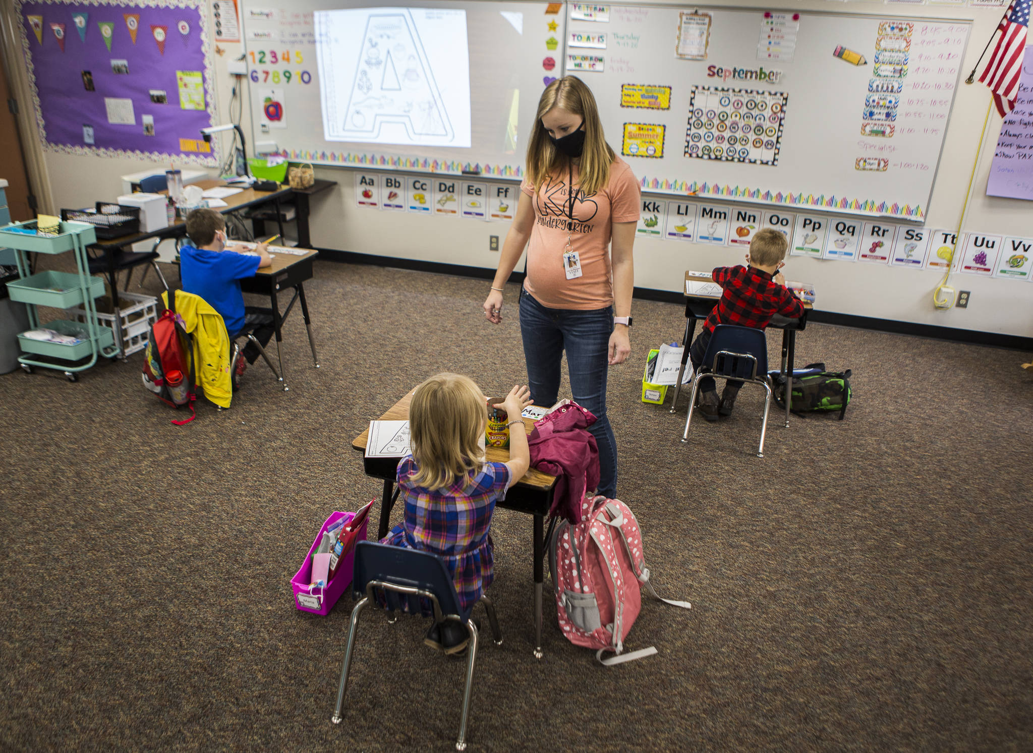 Kari Richards walks around to her three students in class at Twin City Elementary School on Thursday in Stanwood. (Olivia Vanni / The Herald)