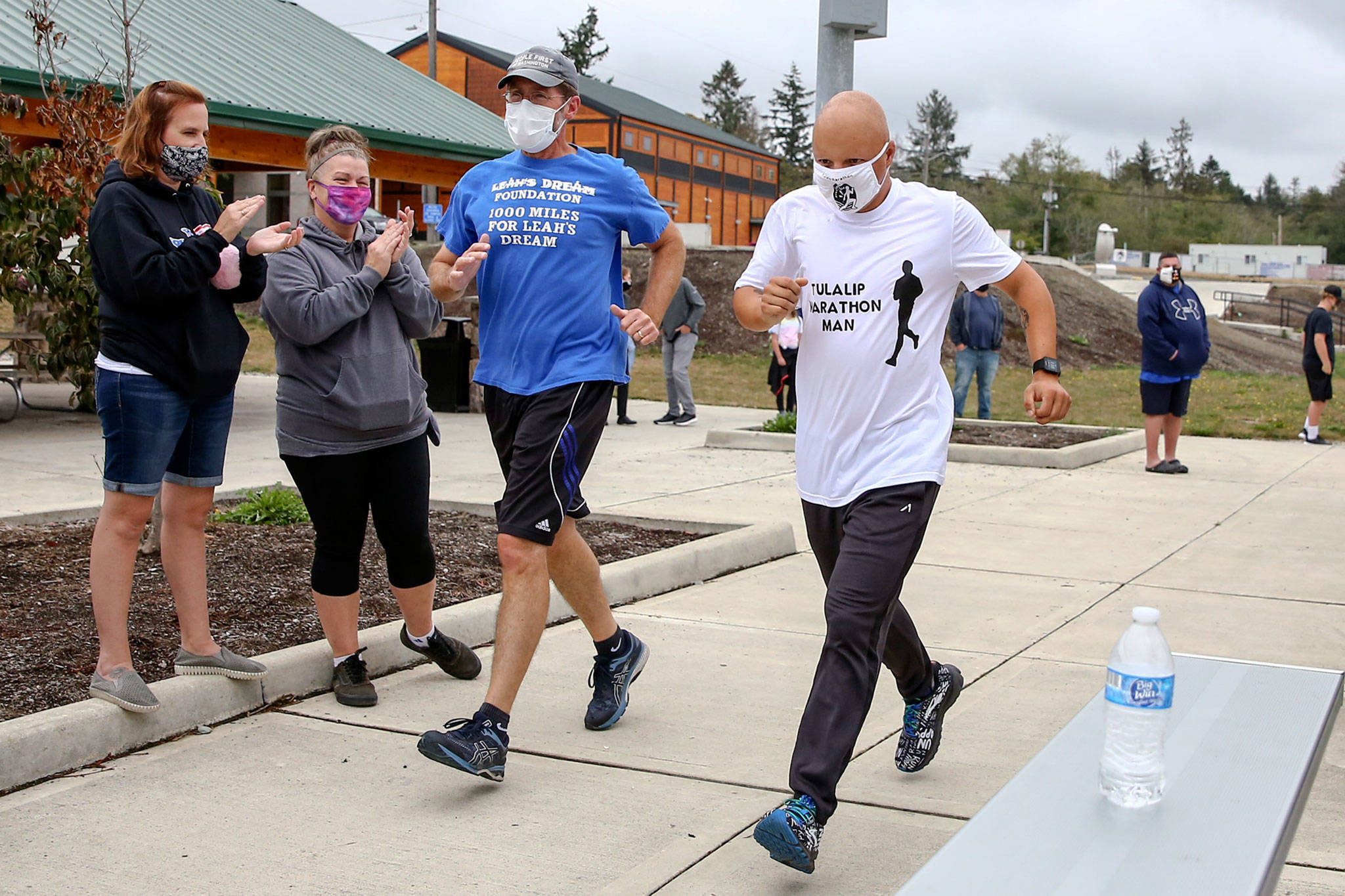 Jim Strickland (left) runs with Tyler Fryberg for the final mile in a 1,000-mile challenge to raise money for Leah's Dream Foundation. (Kevin Clark / The Herald)