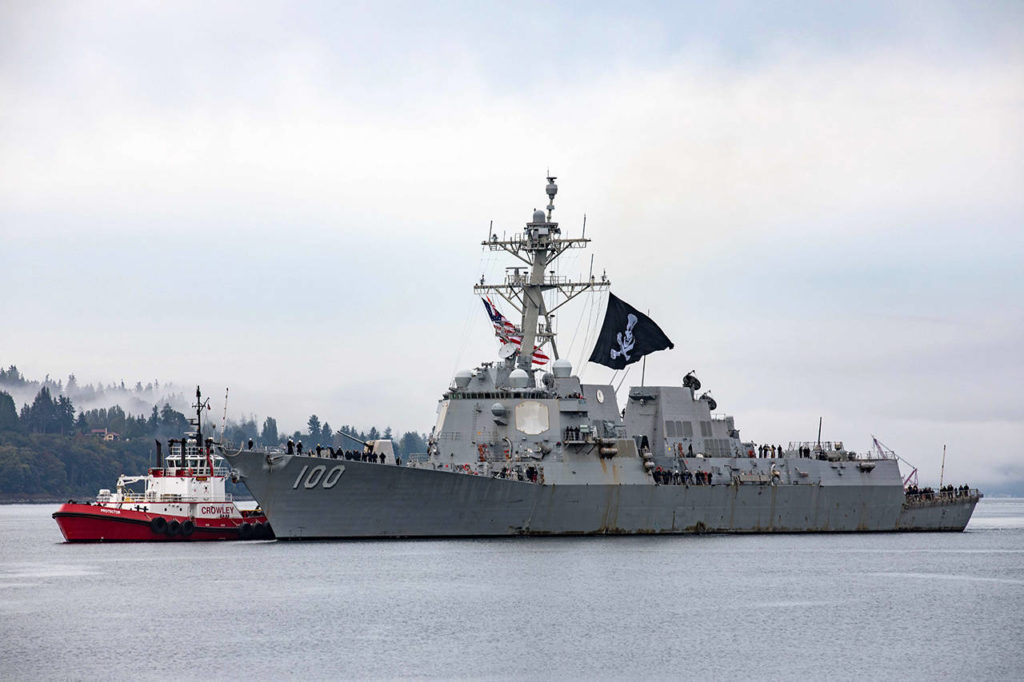 The USS Kidd pulls into its homeport at Naval Station Everett Monday morning, flying a Jolly Roger flag. Dozens on the ship contracted COVID-19 during the nearly nine-month long deployment. (U.S. Navy photo by Mass Communication Specialist 3rd Class Ethan Soto/Released)