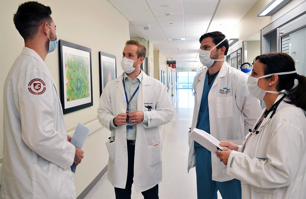 Dr. Matthew Hansen (second from left) on rounds Wednesday at Providence Regional Medical Center Everett. He is director of the new WSU Internal Medicine Residency Program-Everett. With Hansen, from left, are WSU medical student Samuel Josephsen; Matt Anderson, a resident with the Sea Mar Family Medicine Residency Program; and Rosane Fernandez, an internal medicine physician and WSU faculty member. (Wendy Fagan/Providence Regional Medical Center Everett photo)