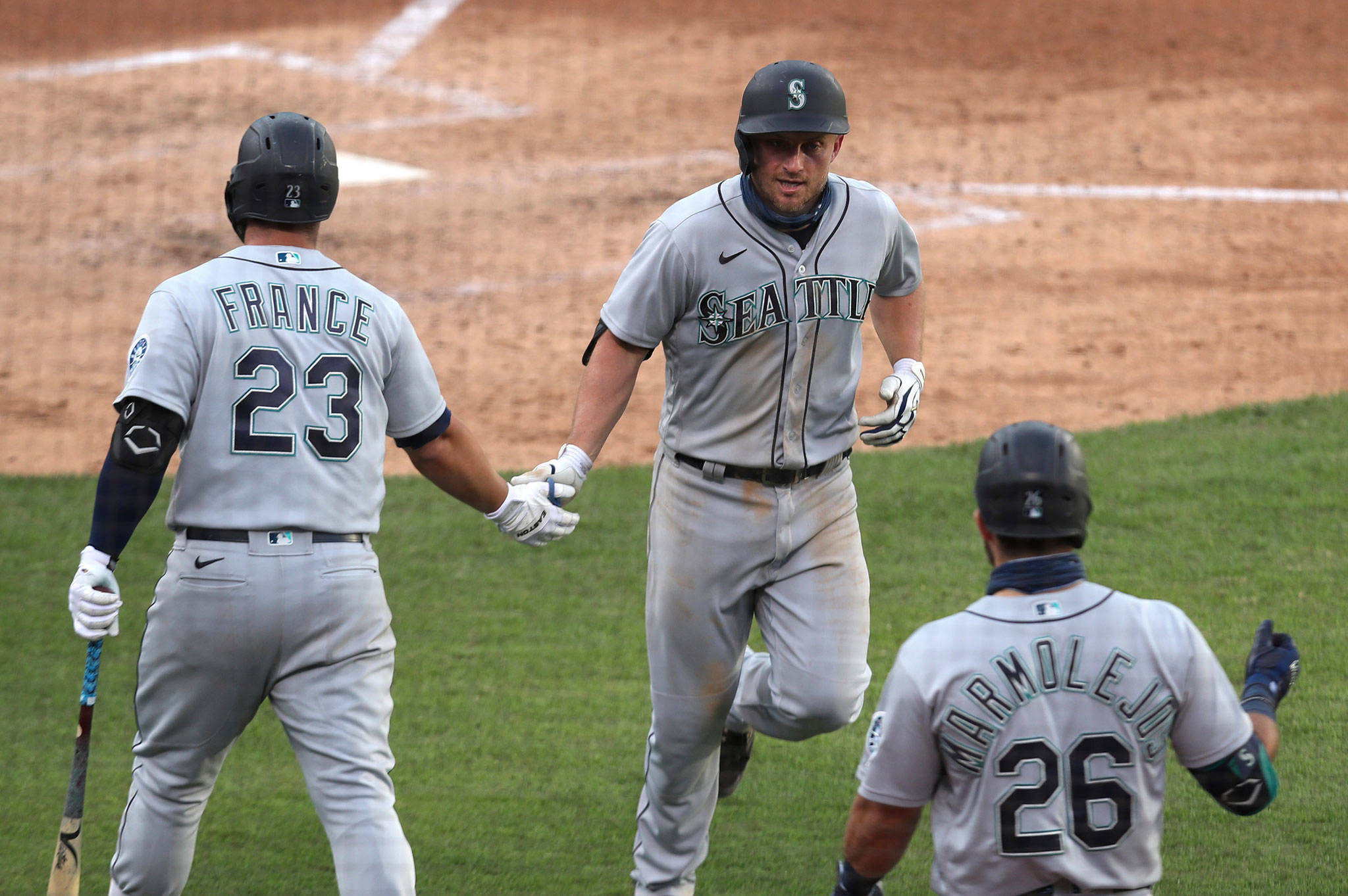 The Mariners' Kyle Seager (center) celebrates with teammates Ty France and José Marmolejos after hitting a solo home run during the fourth inning of the second game of a doubleheader against the Athletics on Sept. 26, 2020, in Oakland, Calif. (AP Photo/Jed Jacobsohn)