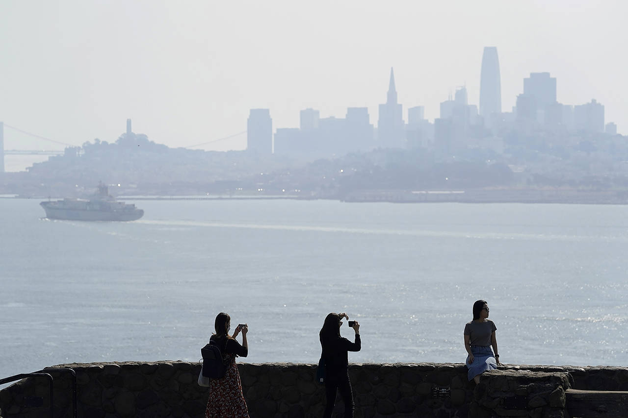 People take pictures at a vista point with the San Francisco skyline obscured by smoke from wildfires and heat in the background Monday near Sausalito, California. (AP Photo/Eric Risberg)