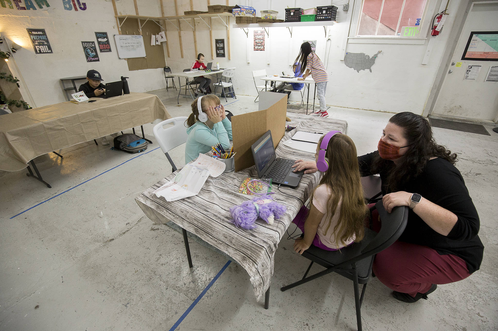 Teacher Shana Brown assists a student with a Zoom meeting while overseeing employees' children engaged in virtual learning in the former warehouse space at the Malicious Women Co. candle shop in Snohomish. (Andy Bronson / The Herald)