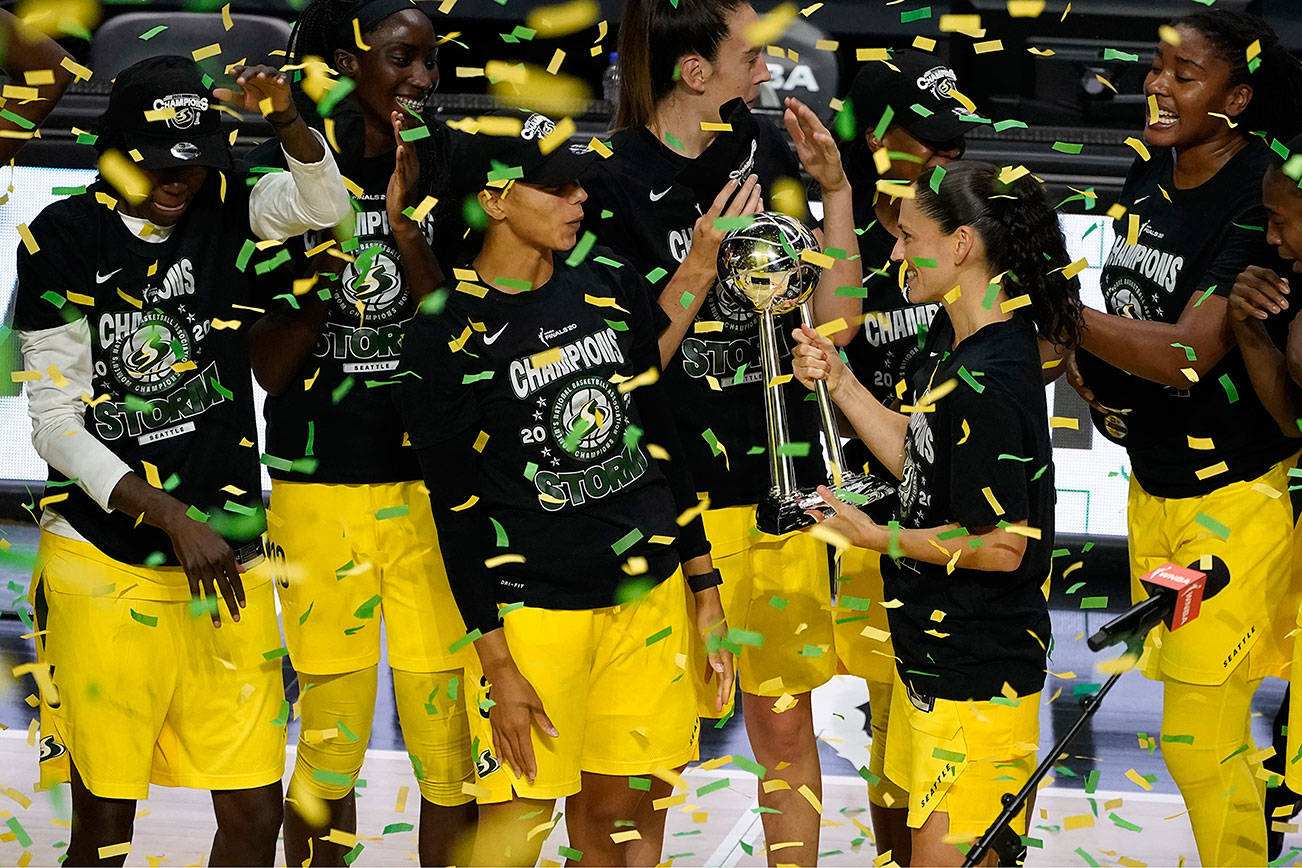Seattle Storm guard Sue Bird shows the trophy to some of her teammates after the team defeated the Las Vegas Aces to win the WNBA championship Tuesday, Oct. 6, 2020, in Bradenton, Fla. (AP Photo/Chris O'Meara)