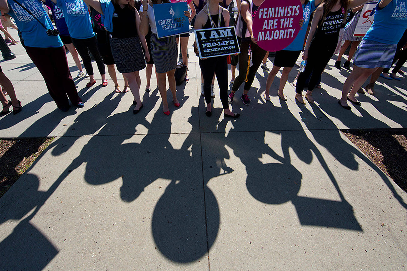 Demonstrators on both sides of the abortion issue stand on the sidewalk in front of the Supreme Court in Washington, Monday, June 20, 2016, as the court announced several decisions. (AP Photo/Alex Brandon)