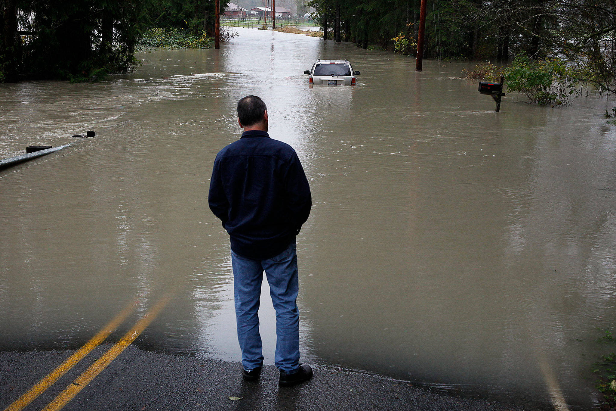 An abandoned car sits Nov. 13, 2015, on flooded Mann Road near Sultan. (Ian Terry / Herald file)