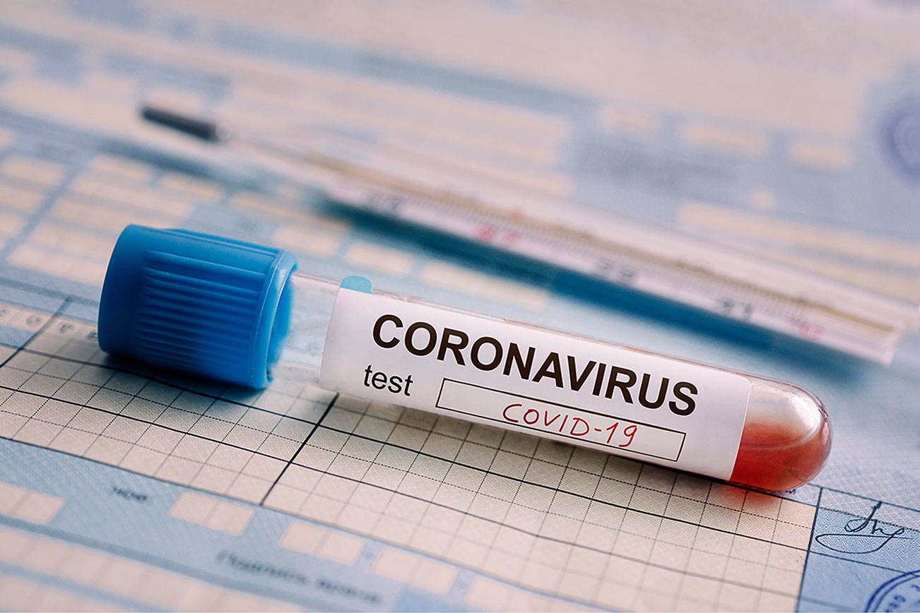 test tube with the blood test is on the table next to the documents. Positive test for coronavirus covid-19. The concept of fighting a dangerous Chinese disease.