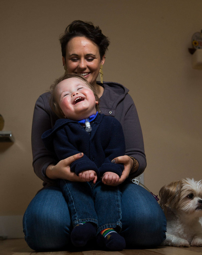 "Malachi Stohr, 2, laughs as his mother Whitney sings the ""Llama Song"" at home Oct. 21 in Lynnwood. Stohr was born with spina bifida. He has spent much of his life at Seattle Children's Hospital. (Andy Bronson / The Herald)"