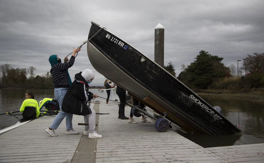 While rowers prep their sculls, the Everett Rowing Association's Hannah Swissa and Sarah Swisa lower a skiff into the water. (Andy Bronson / The Herald)