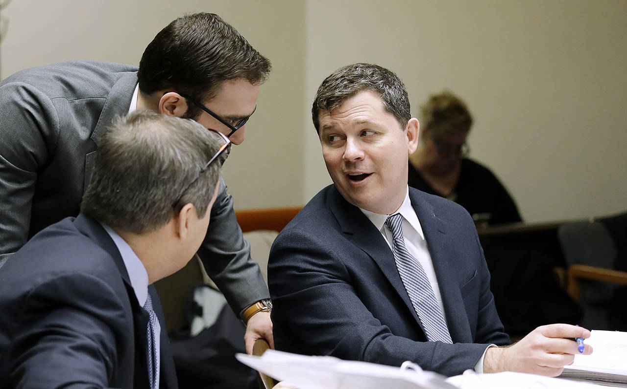 In this 2016 photo, Grocery Manufacturers Association lawyer Matthew Gardner (right) talks with others, before making arguments in a case alleging that the food industry group violated state campaign disclosure laws in opposing a 2013 food labeling initiative, in Olympia. (AP Photo/Elaine Thompson, file)