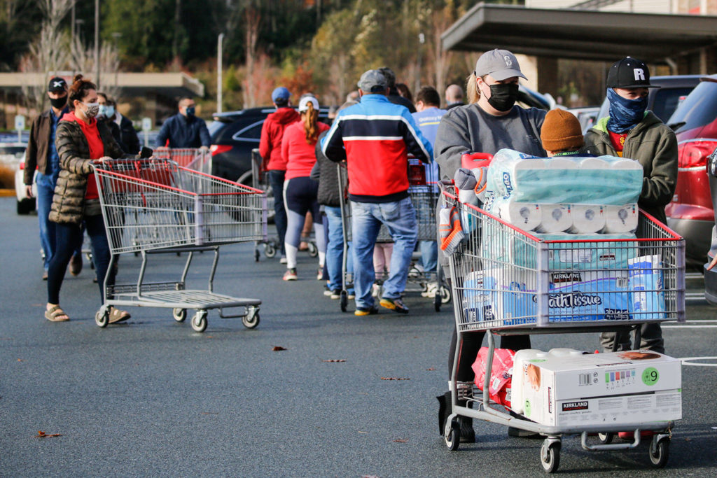 A Costso customer pushes his cart of groceries past others waiting to get in the store Sunday morning in Lynnwood. (Kevin Clark / The Herald)
