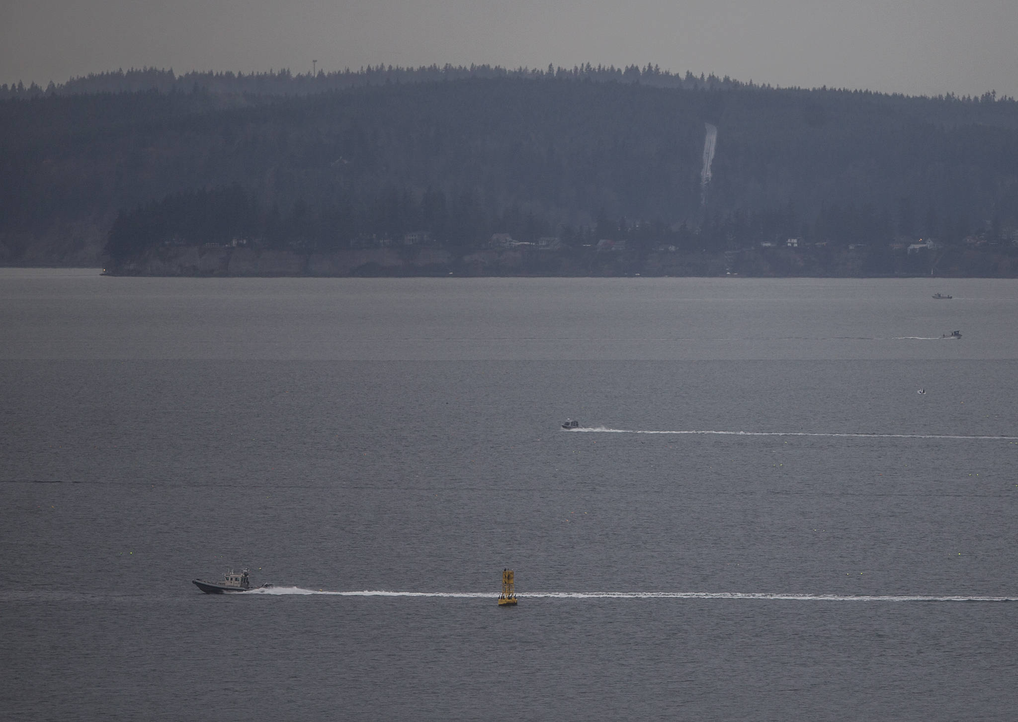 A patrol boat heads across Possession Sound while the search for a Tulalip police officer missing from a capsized Tulalip fisheries boat continues Wednesday near Everett. (Olivia Vanni / The Herald)