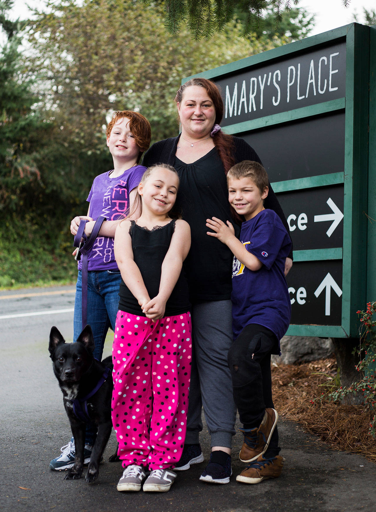 Julie Copeland (center) with her children Lillian, 11, Naomi, 7, and Michah, 9, and their dog Pippin outside of Mary's Place in Burien. (Olivia Vanni / The Herald)