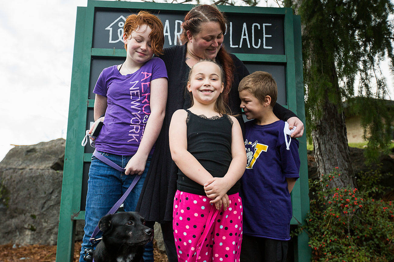 Julie Copeland, center, with her daughters Lillian, 11, Naomi, 7 and son, Michah, 9 with their dog Pippin, 3, outside of Mary's Place on Thursday, Nov. 19, 2020 in Burien, Wa. (Olivia Vanni / The Herald)