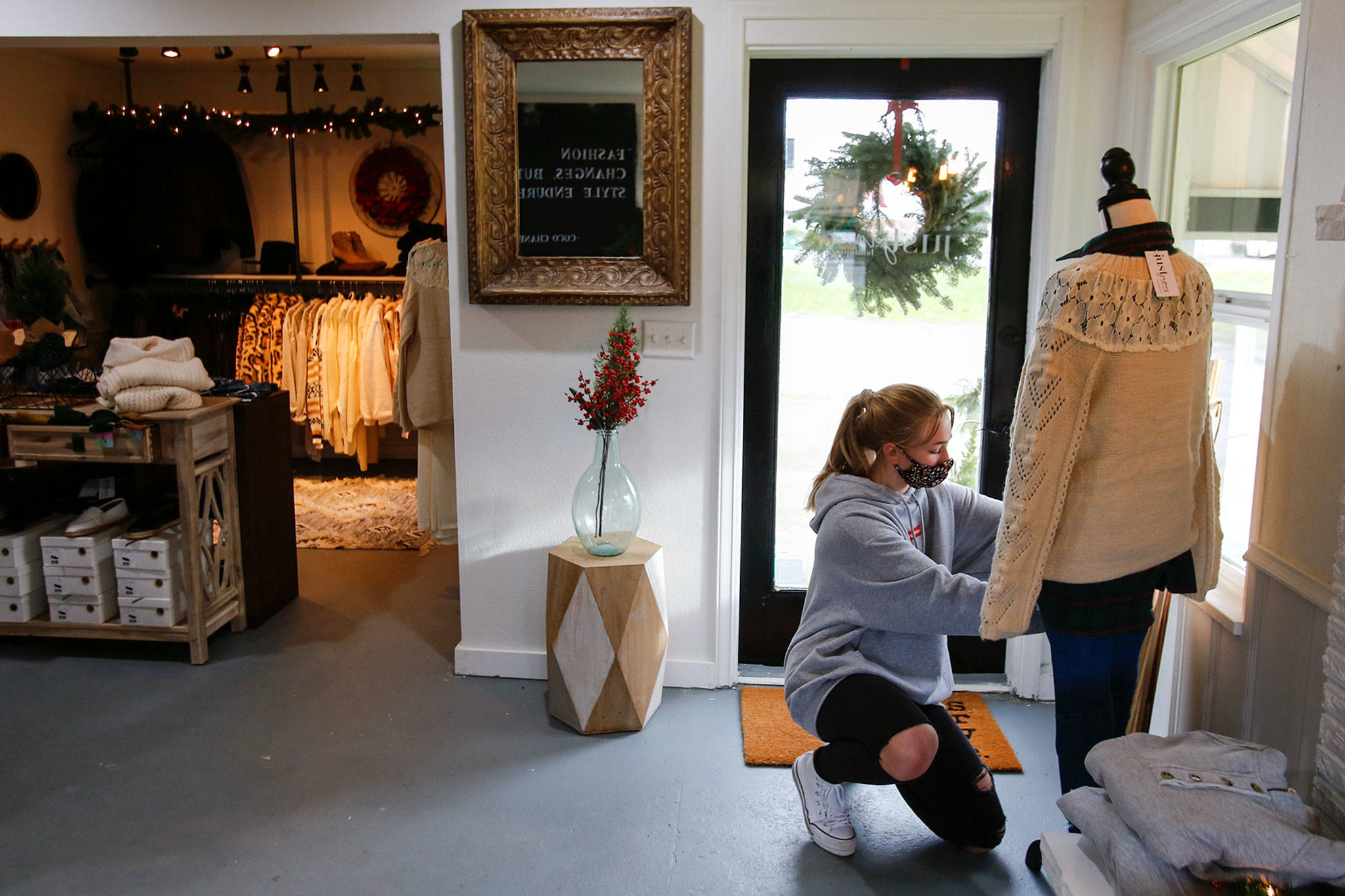 Claire Vondemkamp stages clothing at Just James Boutique in Stanwood. (Kevin Clark / The Herald)