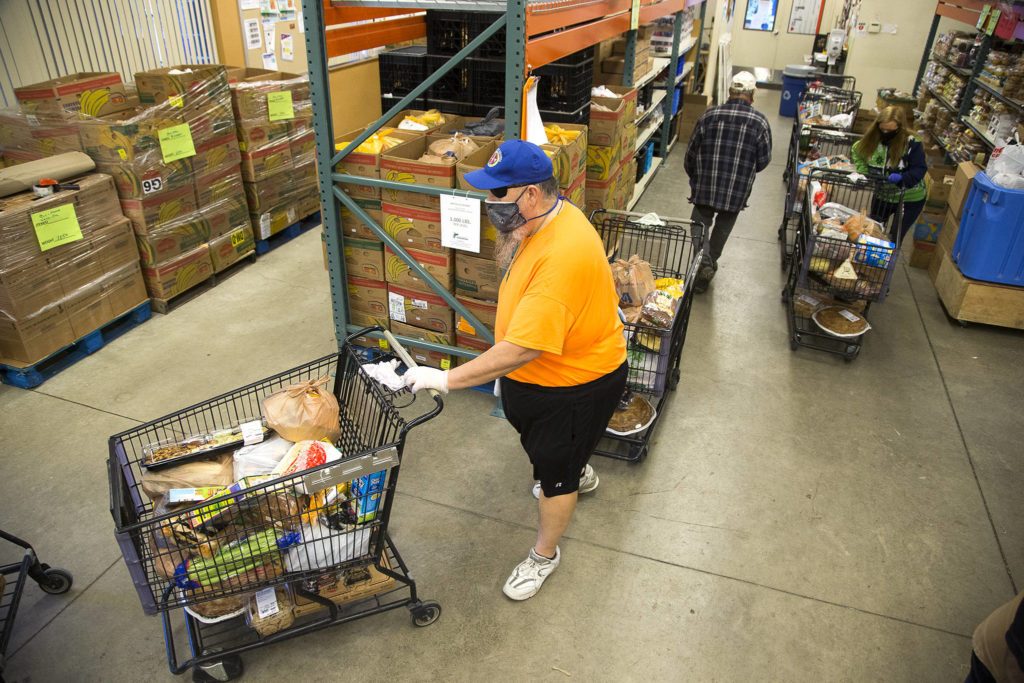 Volunteer Kevin Boldt and Jennifer Chapman direct shopping carts full of food outside at the Marysville Community Food Bank on Nov. 30. (Andy Bronson / The Herald)